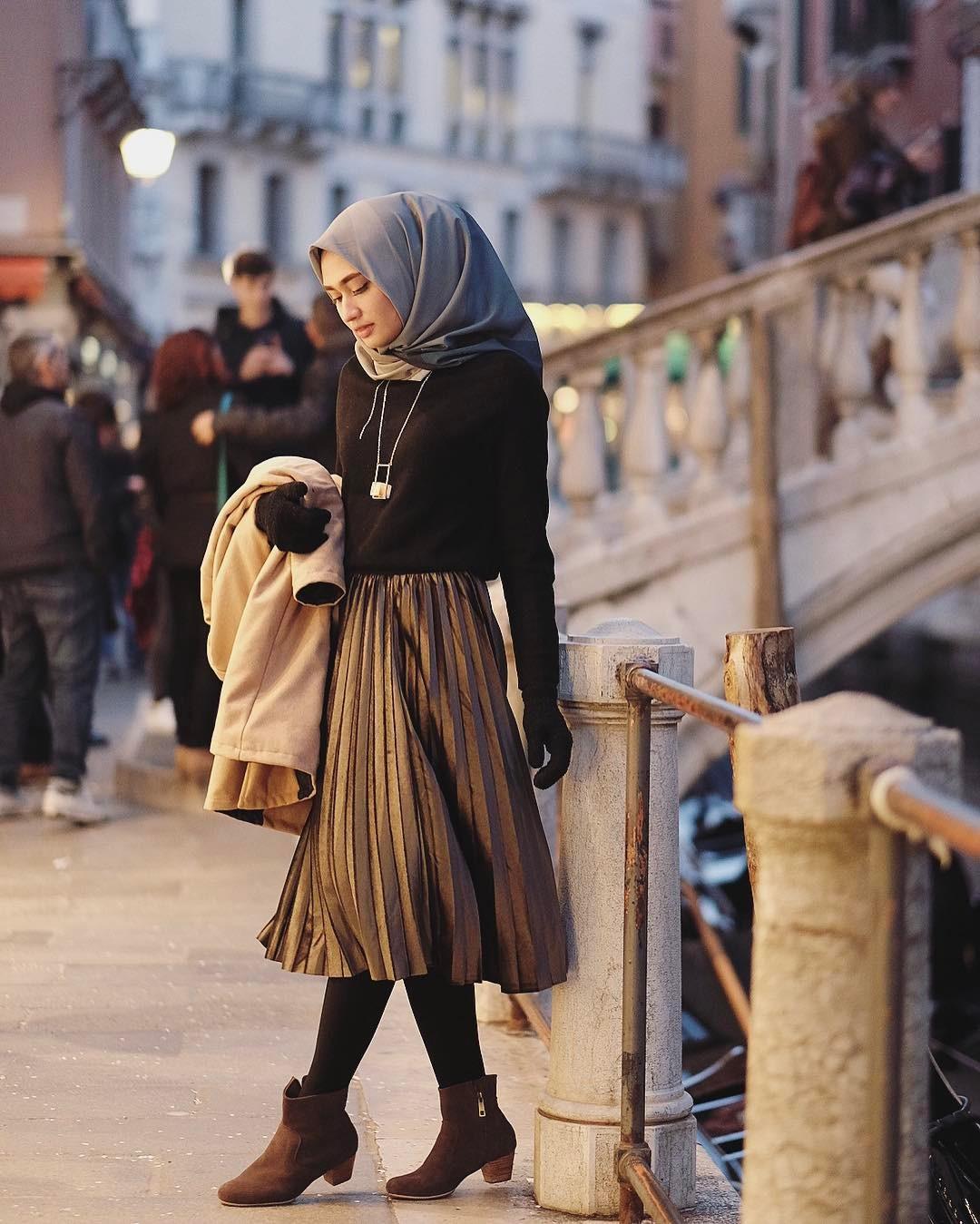 Memadukan midi skirt dengan atasan hitam tangan panjang polos